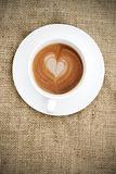 Cup of coffee with heart shape in foam on hessian background Royalty Free Stock Photography