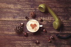 Cup of coffee with heart shape and green handset Stock Photo