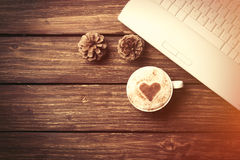 Cup of coffee with heart shape and laptop computer Royalty Free Stock Photo