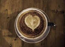 Cup of coffee with heart shape in it. made out of froth, wooden Stock Images