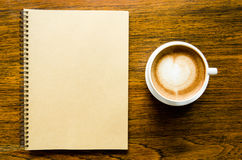 Cup of coffee with heart shape and open blank book Stock Photos