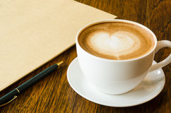 A cup of coffee with heart shape, pen and blank book Royalty Free Stock Photography