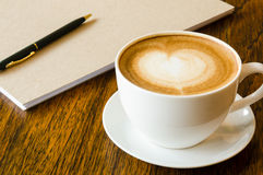 A cup of coffee with heart shape, pen and blank book Royalty Free Stock Photo