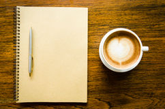 A cup of coffee with heart shape, pen and blank book Royalty Free Stock Photos