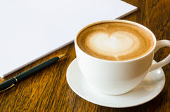 A cup of coffee with heart shape, pen and open blank book on wood  background Stock Photos