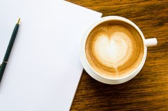 A cup of coffee with heart shape, pen and open blank book Stock Photos