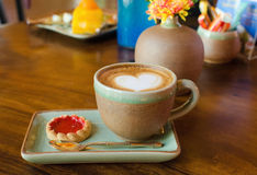 Cup of coffee, heart shape with strawberry biscuit on wood Royalty Free Stock Images