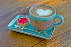 Cup of coffee, heart shape with strawberry biscuit on wood backg Royalty Free Stock Photo