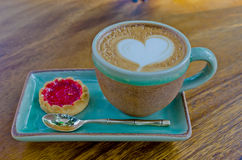 Cup of coffee, heart shape with strawberry biscuit on wood backg Royalty Free Stock Images