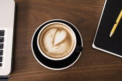 A cup of coffee with heart shape on wooden work table. With notebook, pencil and laptop. Top view stock image