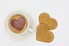 Cup of coffee with heart shaped pattern and cookies. Cup of coffee with heart shaped cinnamon pattern and few heart shaped cookies. Space on the top can be used Royalty Free Stock Photos