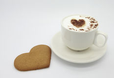 Cup of coffee with heart shaped pattern and ginger cookie. Cup of cappuccino with heart shaped cinnamon pattern on milk foam and ginger heart shaped cookie stock photo