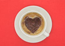 Cup of coffee with heart shaped pattern on red background. Cup of coffee with heart shaped cinnamon pattern on red background royalty free stock photography