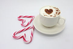 Cup of coffee with heart shaped pattern and red candies. Cup of cappuccino with heart shaped cinnamon pattern on milk foam, view from above. And red candy cannes stock photo