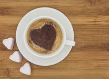 Cup of coffee with heart shaped pattern on wooden background. Cup of coffee with heart shaped cinnamon pattern with few marshmallow hearts on wooden background royalty free stock photos