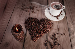 A cup of coffee with heart shaped stack of coffee and coffe candle Stock Photo