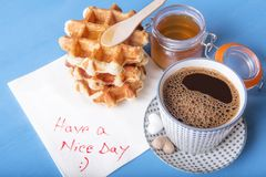 Tasty breakfast and napkin message. Cup of coffee with heart shaped sugar, homemade waffles with honey and a napkin with have a nice day message, on a blue Royalty Free Stock Images
