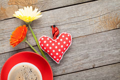 Cup of coffee, heart toy and gerbera flowers on wooden table Stock Image