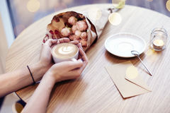 Cup of coffee with heart in woman hands, envelope and flowers on wooden table in cafe. Bokeh on background. Focus on left hand. Cup of coffee with heart in Stock Images