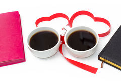 Cup of coffee, hearts of red ribbon, pink and black diaries on white background. Royalty Free Stock Images