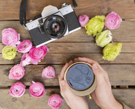 A cup of coffee held in two hands on a wood table with a classic photo camera around with colorful flowers Stock Photos
