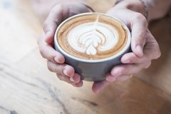 A cup of coffee hold on women's hands that have top by foamed.  royalty free stock photography