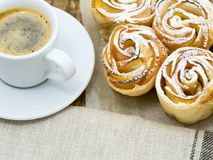 Cup of coffee and homemade pastries of flaky unleavened dough with apples. On parchment paper Stock Image