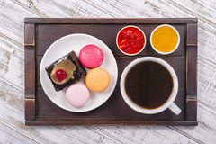 Cup of coffee, honey, strawberry jam, piece chocolate cake and macaron cakes on tray on white wooden table. Lifestyle concept. Stock Image