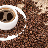 Cup of coffee. Cup of hot coffee with beans abound it Stock Image
