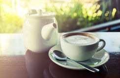 Cup of coffee with hot tea pot on wooden and blur background Stock Images