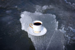 Cup of coffee on ice. Hot coffee in a cup on a saucer on cold ice Stock Images