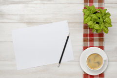 Cup of coffee and indoor plant are on a checkered tablecloth with white paper, pencil next to them. Royalty Free Stock Photos