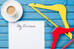 Cup of coffee and inscription on a paper near hangers Royalty Free Stock Photos