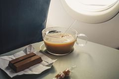 Cup with coffee interior of airplane. Cup with coffee interior of airplane on the background of the plane window on the folding table Stock Images