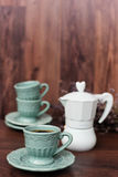 Cup of coffee and Italian coffee maker in blue, scent of lavender. Dark background Royalty Free Stock Photography