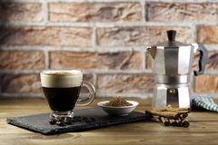 Cup of coffee and Italian coffee maker. Cup of coffee, Italian coffee maker, coffee beans, cinnamon and napkin on wood table and brick background Stock Photography
