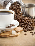 Cup of coffee and jar with beans Stock Photos