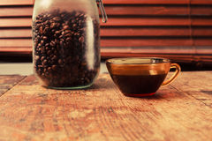 Cup of coffee and jar of beans by window Royalty Free Stock Image
