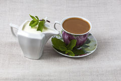 Cup of coffee and a jar of cream. Cup of coffee on a saucer and a jar of cream, decorated with mint leaves on a background of gray fabric from  flax Royalty Free Stock Photography