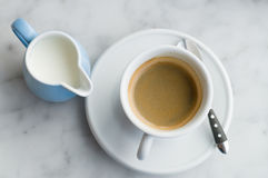 Cup of coffee and jug of milk. From above view Royalty Free Stock Photography