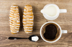 Cup of coffee, jug milk, eclairs and spoon on table Royalty Free Stock Photography