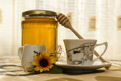 Cup of coffee with a jug of milk and honey on the table. Room in sunlight Stock Image