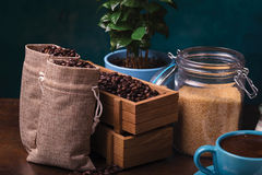 cup of coffee and jute bags, wooden container, cane sugar Royalty Free Stock Photos