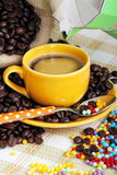 Cup of coffee. Jute sack and grains of coffee with colored sugar pearls on background of colored cloth e coffee maker Royalty Free Stock Image