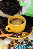 Cup of coffee. Jute sack and grains coffee and cup with colored sugar pearls and a coffee maker on colored cloth as background Royalty Free Stock Photography