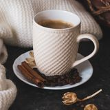 A cup of coffee is the key to a good mood. On a black, dark textural background, a composition of white, cream scarf and a white stock photos