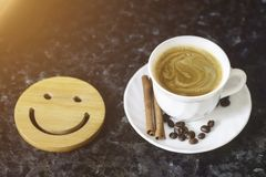 A cup of coffee is the key to a good mood. Wooden smiley on a dark, black, textural background. On the edge you can see a white stock images