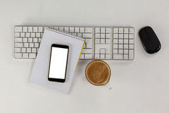 Cup of coffee with keyboard, mobile phone and mouse Stock Image