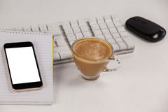 Cup of coffee with keyboard, mobile phone and mouse Royalty Free Stock Photo