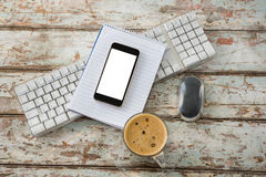 Cup of coffee with keyboard, mobile phone and mouse Royalty Free Stock Images